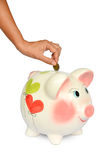 Piggy bank and hand with coin isolated Stock Photo