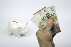 Piggy bank and hand holding money on white background Stock Photo