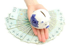 Piggy bank on hand of woman and banknotes. White background Royalty Free Stock Images