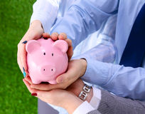 Piggy Bank in hands of a family Royalty Free Stock Photography