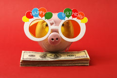 Piggy bank with Happy birthday party glasses standing on stack of money american hundred dollar bills on red background Royalty Free Stock Photos