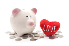 Piggy bank with heart and coin on white background Royalty Free Stock Image