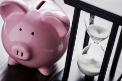 Piggy bank with an hour glass Royalty Free Stock Photos