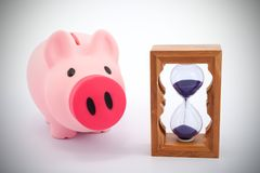 Piggy bank and hourglass Stock Images