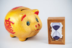 Piggy bank and hourglass Royalty Free Stock Photo