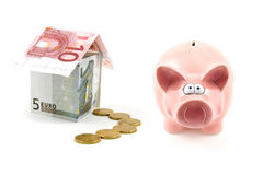 Piggy bank and house of banknotes Royalty Free Stock Images