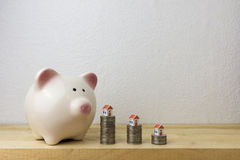 Piggy bank with house and coins Stock Photography