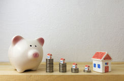 Piggy bank with house and coins Royalty Free Stock Photos