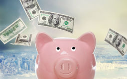 Piggy bank with hundred dollar bills. Above the city Stock Photos