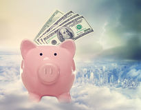 Piggy bank with hundred dollar bills above the city. Piggy bank with us dollar bills on a cloud above the city Royalty Free Stock Photos