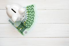 Piggy bank with hundred euro bills Royalty Free Stock Photo