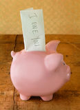 Piggy Bank with IOU Note. Piggy bank with an IOU note sticking out the top Stock Photography