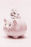 Piggy bank and jigsaw puzzles financial disarray. Conceptual image of jigsaw puzzle pieces inserted into piggy bank - financial disarray royalty free stock photos