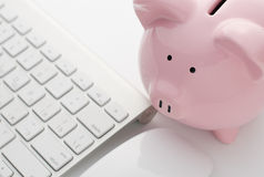 Piggy Bank and Keyboard on Top of White Table Stock Photography