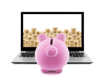 Piggy bank and laptop with stacks of golden coins Stock Photography