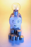 Piggy Bank and Lightbulb Stock Images