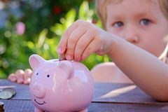 Piggy bank and little boy with coin on colorful background, close up. Family, children, money, investments and people concept - close up of father and daughter Stock Photos