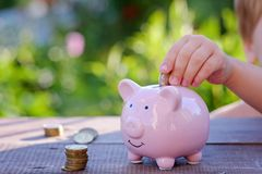 Piggy bank and little boy with coin on colorful background, close up. Family, children, money, investments and people concept - close up of father and daughter Royalty Free Stock Images