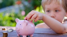 Piggy bank and little boy with coin on colorful background, close up Royalty Free Stock Photo