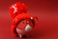 Piggy bank in love with red heart sunglasses with red hat and pom-pom standing on red background Royalty Free Stock Photos