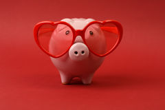 Piggy bank in love with red heart sunglasses  Stock Photo