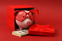 Piggy bank in love with red heart sunglasses standing in gift box with ribbon and with stack of money american hundred dollar bill. S on red background Royalty Free Stock Photos