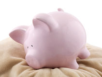 Piggy bank lying down on a pillow Stock Photos