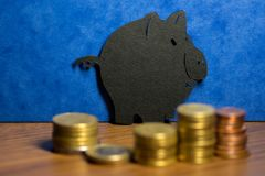 A piggy bank made of black cardboard and a stack of euro coins i royalty free stock images