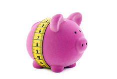 Piggy bank with measure tape Stock Images