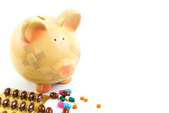 Piggy bank with medical patches and pills Stock Image