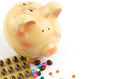 Piggy bank with medical patches and pills Stock Photos
