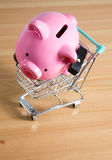 Piggy bank on a miniature shopping cart Stock Photos