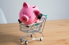 Piggy bank on a miniature shopping cart Stock Photography