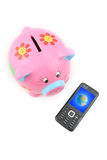 Piggy bank and Mobile Phone. Piggy bank and a sleek mobile phone with a picture of globe on screen Stock Images