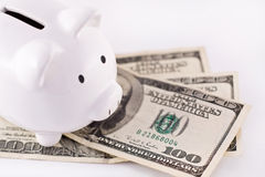 Piggy bank and money. White piggy bank and money ready to go inside it; selective focus on the dollars Stock Photo