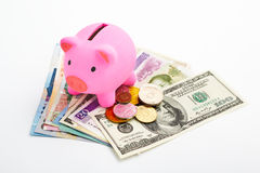 Piggy bank and money. Pink piggy bank and money from several countries over white background Stock Photography