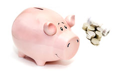 Piggy bank and money. Closeup of pink piggy bank with pile of coins and banknotes, isolated on white background Stock Photos