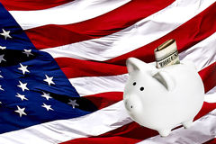 Piggy bank with Money on an American Flag Royalty Free Stock Image