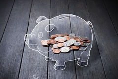 Piggy Bank Money Coins. An abstract piggy bank with a pile of coins on a wood background Stock Images