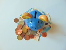 Piggy bank with money and coins. Piggy bank standing on money with coins stock photo