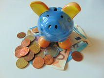 Piggy bank with money and coins. Piggy bank standing on money with coins stock image