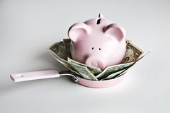 Piggy bank and money in frying pan Royalty Free Stock Photos