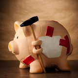 Piggy bank with money and hammer. On tabletop Royalty Free Stock Image