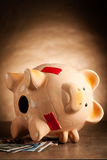 Piggy bank with money and hammer Royalty Free Stock Photo