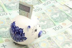 Piggy bank and money on heap of banknotes Royalty Free Stock Photography