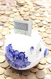 Piggy bank and money on heap of coins Royalty Free Stock Photography