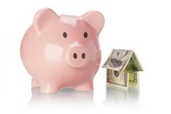 Piggy bank and money house. On white backgound Royalty Free Stock Photos