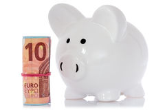 Piggy bank with money roll. On white background Royalty Free Stock Images