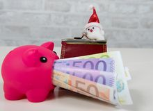 A piggy bank and money with Santa Claus Stock Image