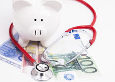 Piggy bank money and stethoscope. Image shows a piggy bank with stethoscope and cash Stock Images